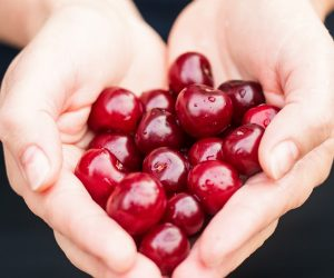 person holding cherries in their cupped hands