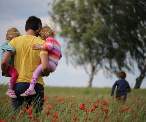 father holding two children while another child runs in the distance