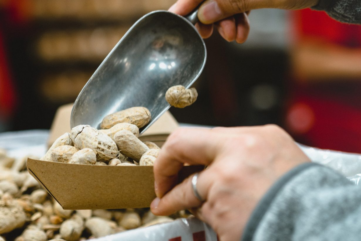 person scooping peanuts into a container