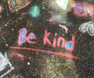 Be Kind written in sidewalk chalk on the ground