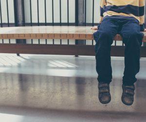 little boy sitting alone on a bench