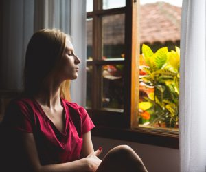 woman sitting by a window looking serene