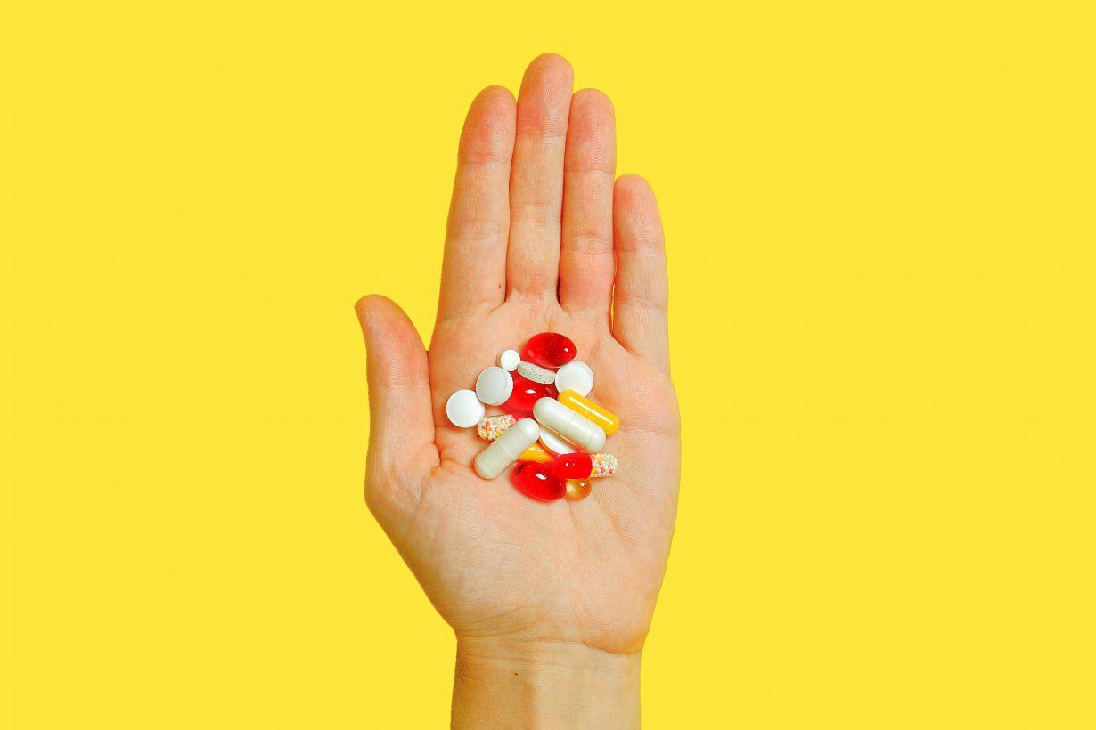 hand full of antibiotics with yellow background