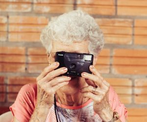 old woman holding a camera up to her face