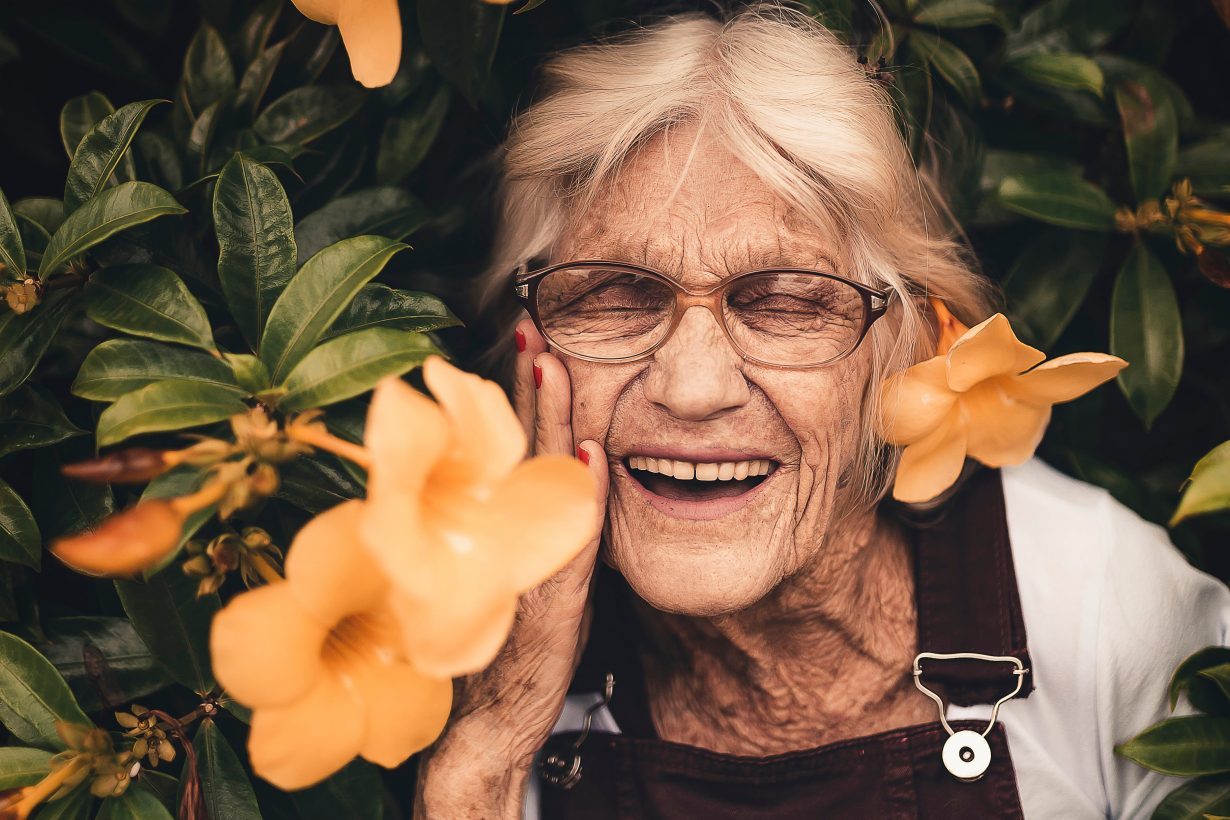 old woman smiling in flowers
