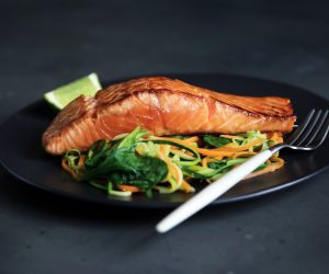 salmon fillet on a bed of vegetables on a black plate