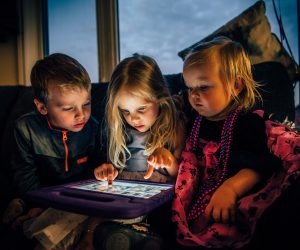children looking at the screen of a tablet