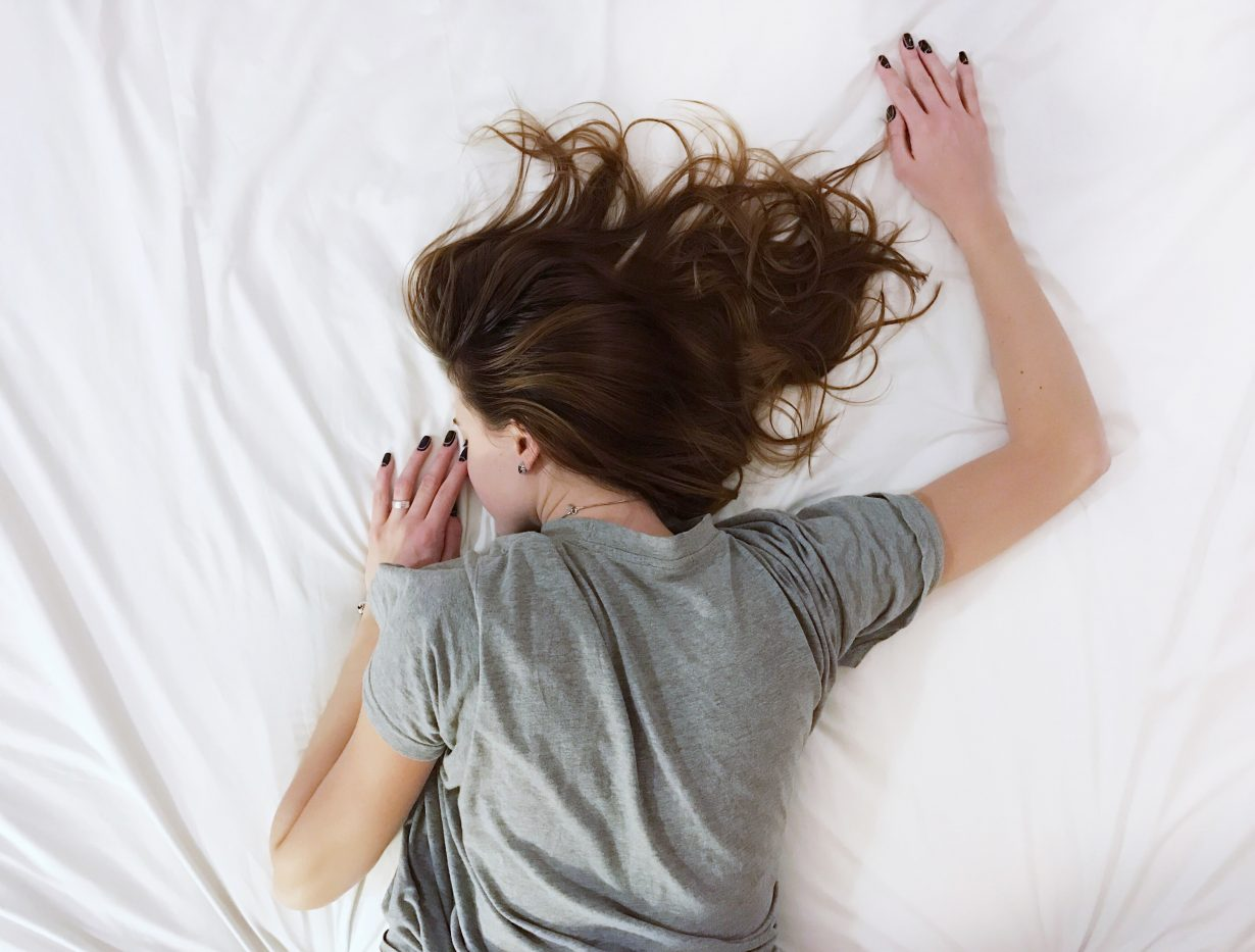 woman sleeping on a white bed