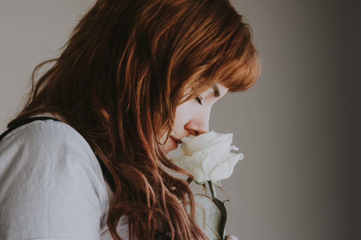 woman sniffing white flower