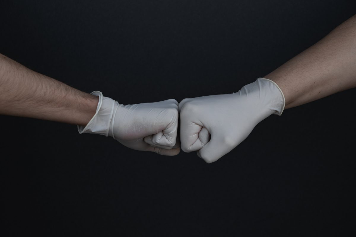 gloved hands giving a fist bump