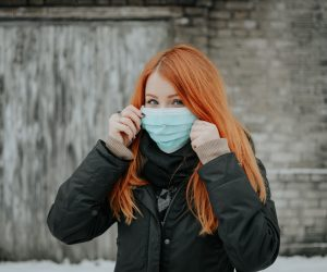 woman holding a mouth guard face mask up to her face