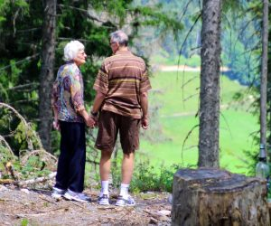old woman and man holding hands in a forest
