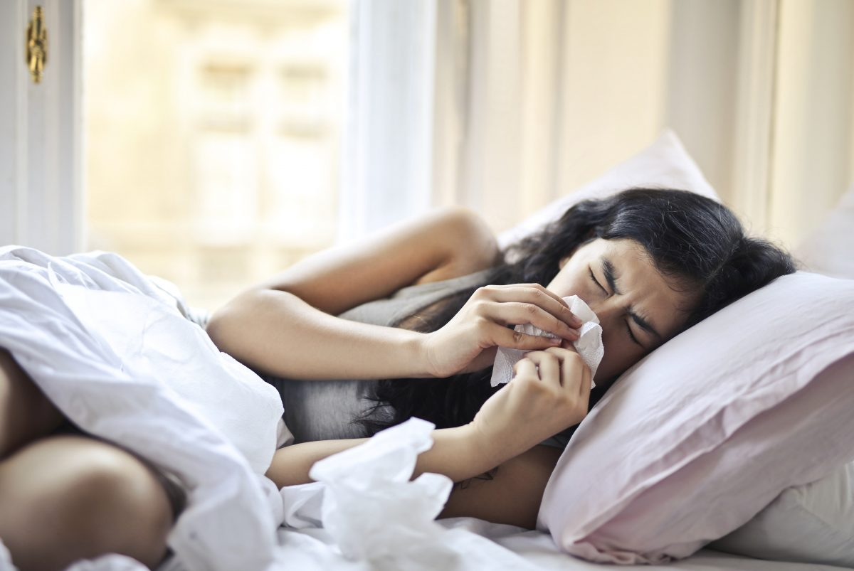 woman laying on her bed blowing her nose