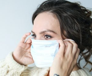 woman putting on surgical mask