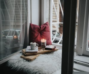 window seat with books and coffee and a candle
