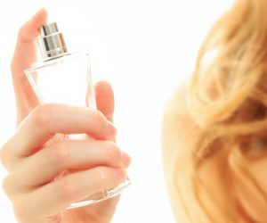 woman spraying herself with perfume
