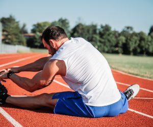 man stretching on a runners track