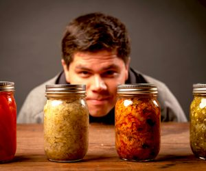 man looking at jars of fermented vegetables