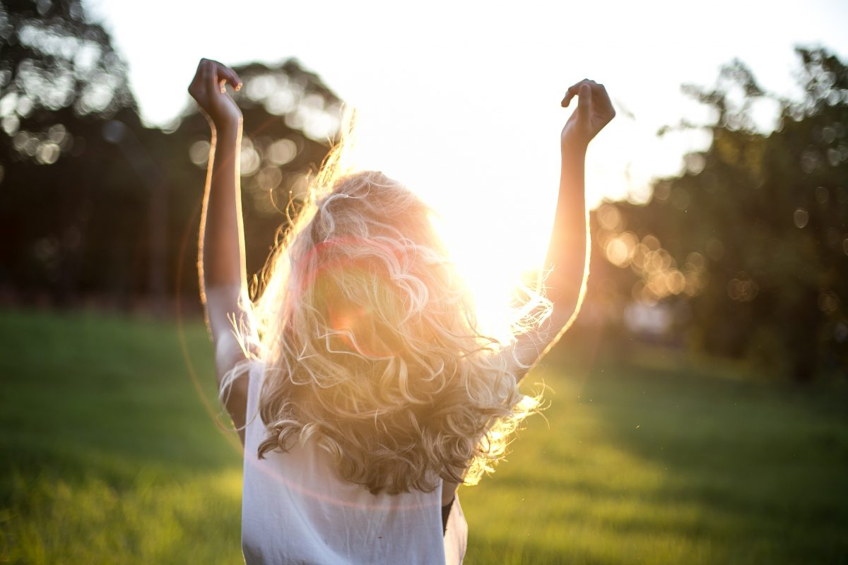 woman standing with arms raised facing the sunshine