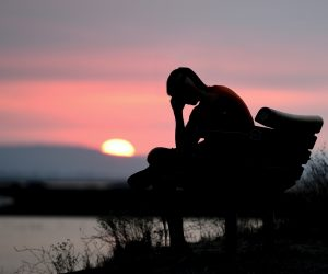 silhouette of a person sitting on a bench holding their head