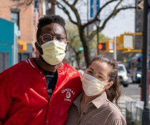 two people smiling with face masks on