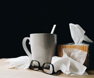 mug, glasses and nose tissues on a table