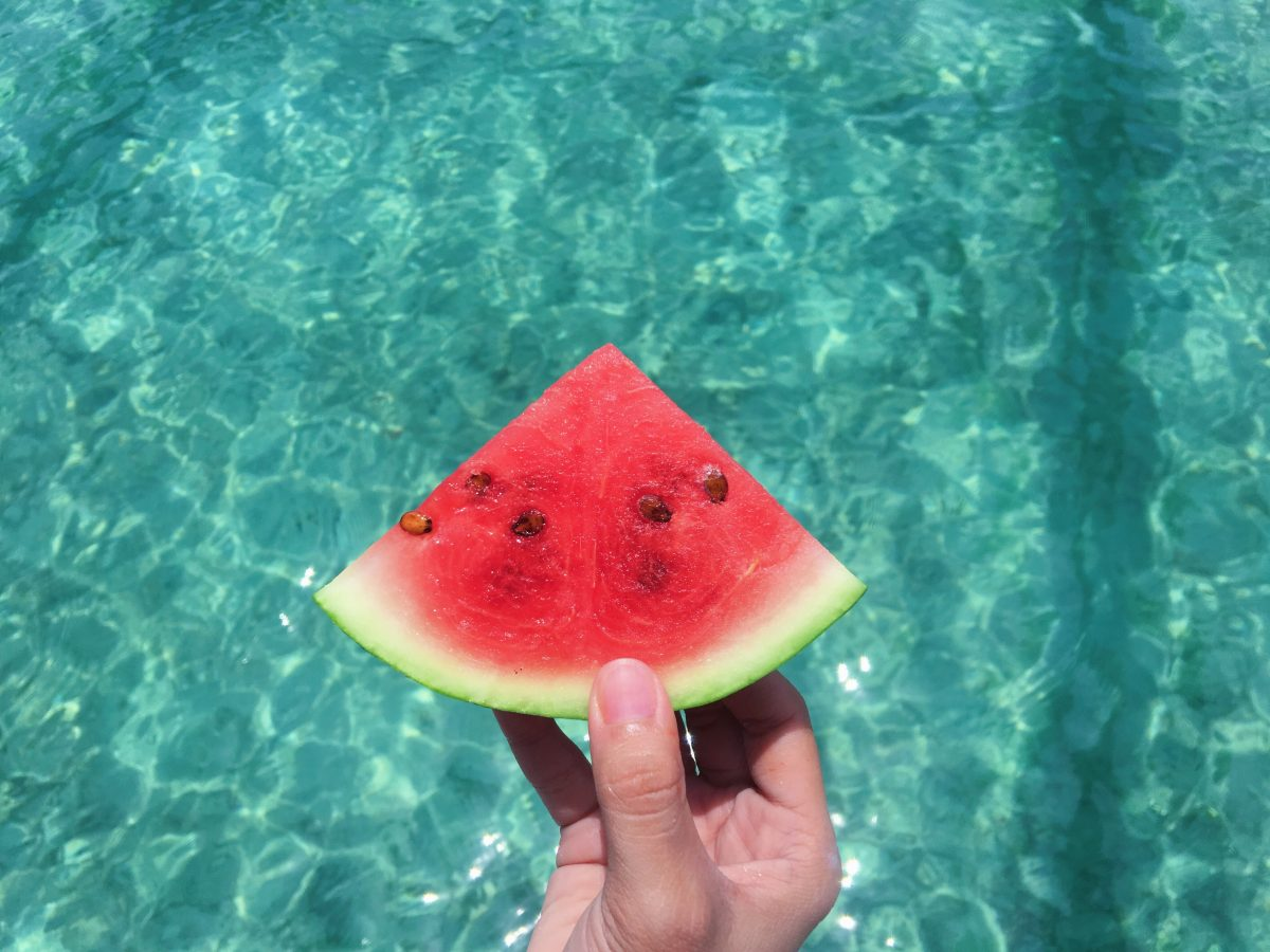 person holding a watermelon slice above aqua colored water