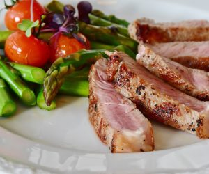 a white plate with steak fillets and asparagus on it
