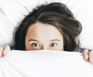 woman lying in a bed with the sheets pulled up to her face