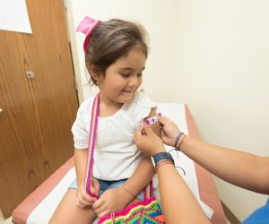 Little girl getting her bandaid put on her arm