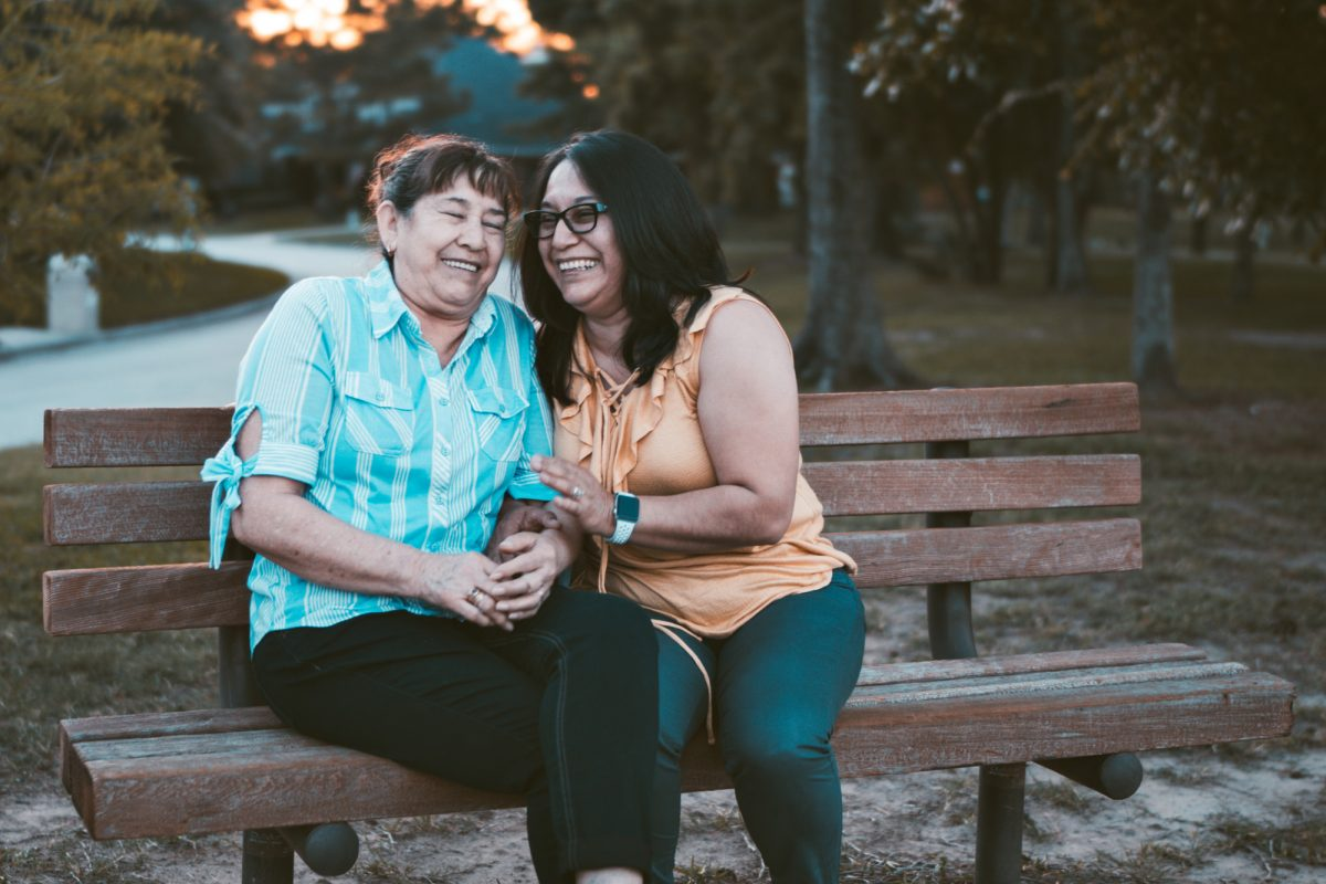 two women sitting on a park bench laughing together