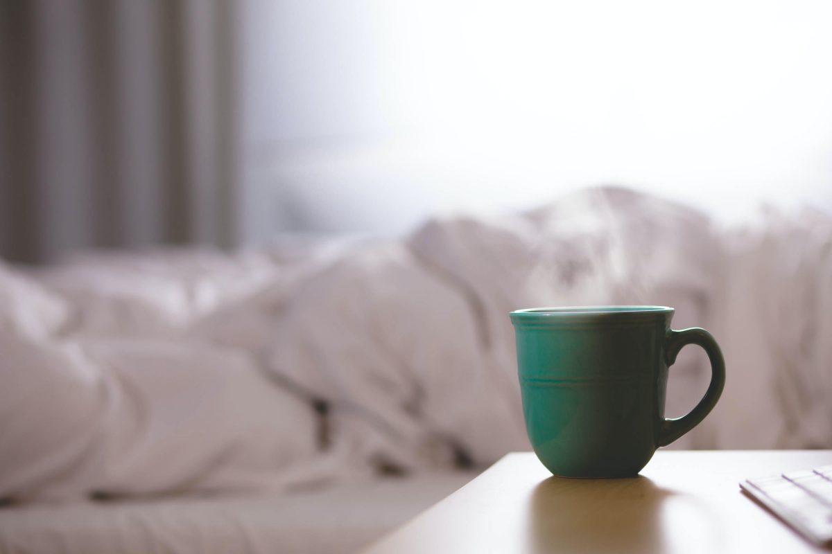 mug of tea next to an empty bed