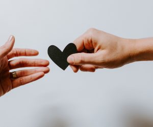 male and female hands holding a heart together