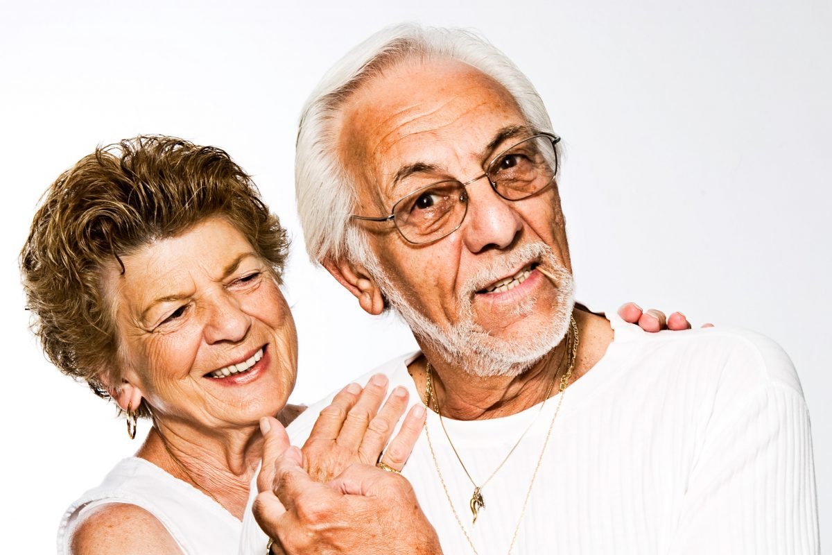 older man and woman posing together