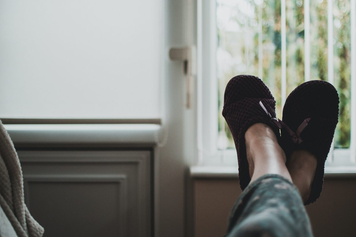 person lounging with their feet in slippers