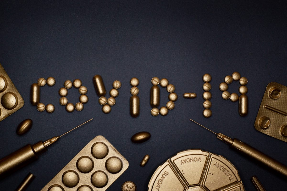 COVID-19 written in gold sprayed pills