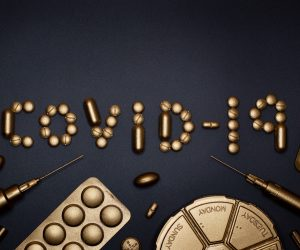 COVID-19 written in gold sprayed pills