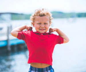 little boy flexing for the camera