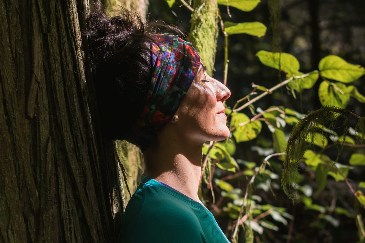 woman leaning against a tree with eyes closed