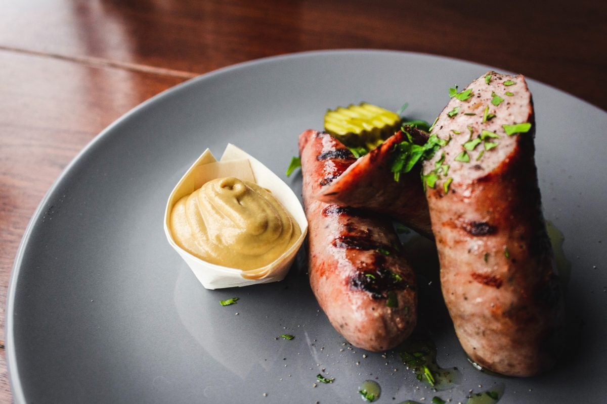 cooked sausage on a plate with mustard