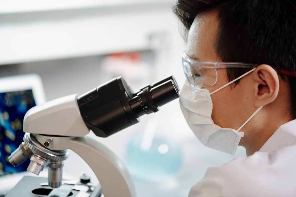 man looking through microscope in a medical lab