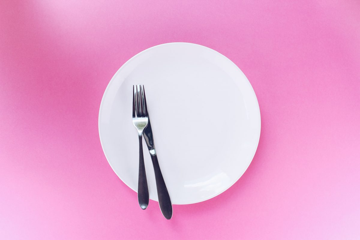 empty white plate with silverware against a pink backdrop