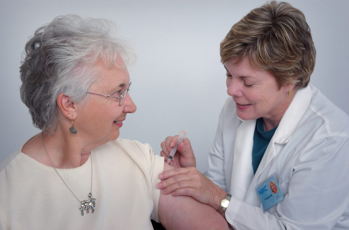 older woman getting a shot from a doctor