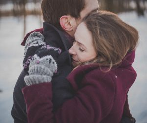 man and woman hugging while standing in snow