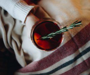 a person holding a mug of rosemary tea